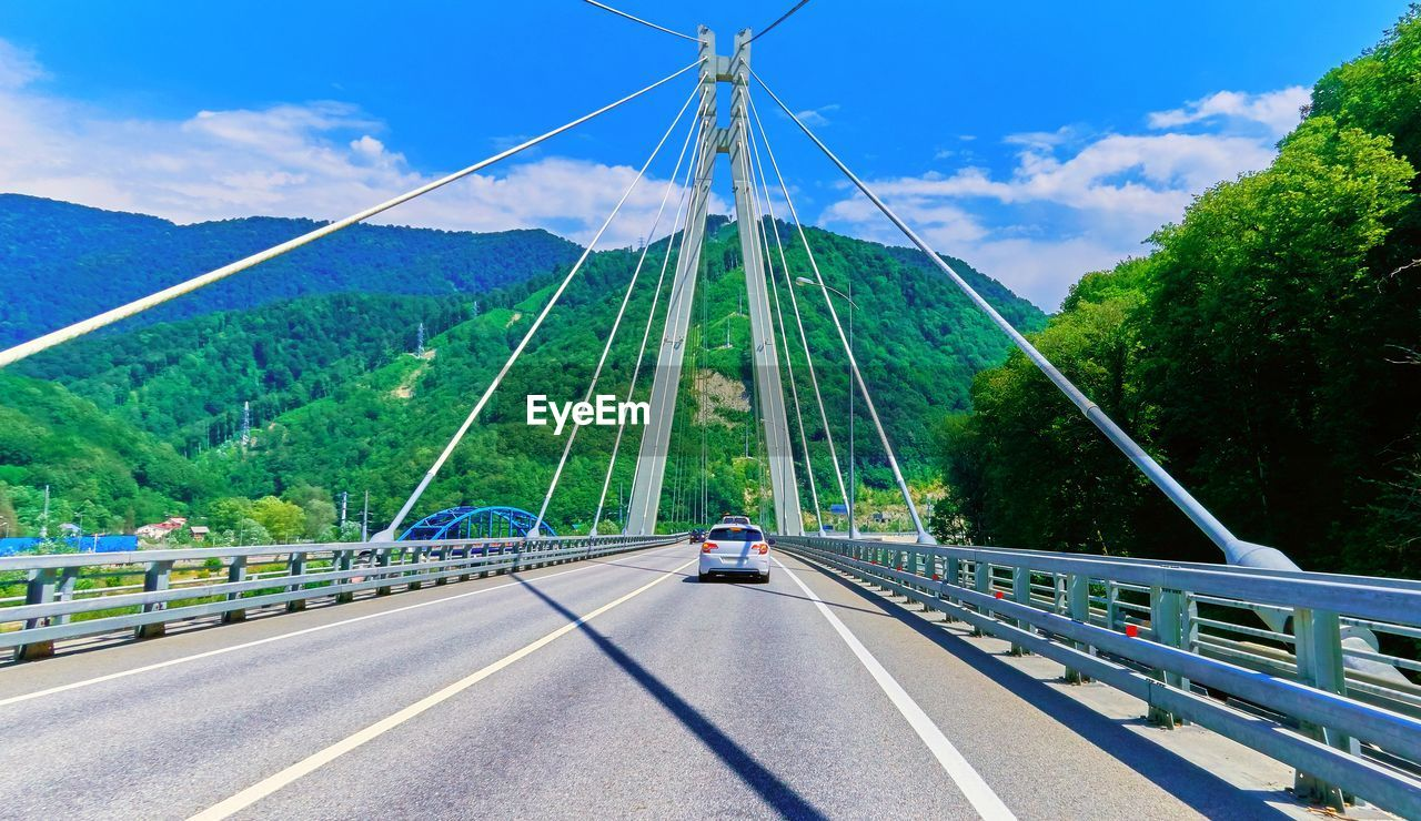 transportation, bridge, road, sky, connection, bridge - man made structure, the way forward, direction, cloud - sky, car, railing, nature, plant, built structure, motor vehicle, symbol, marking, no people, diminishing perspective, mode of transportation, outdoors, crash barrier