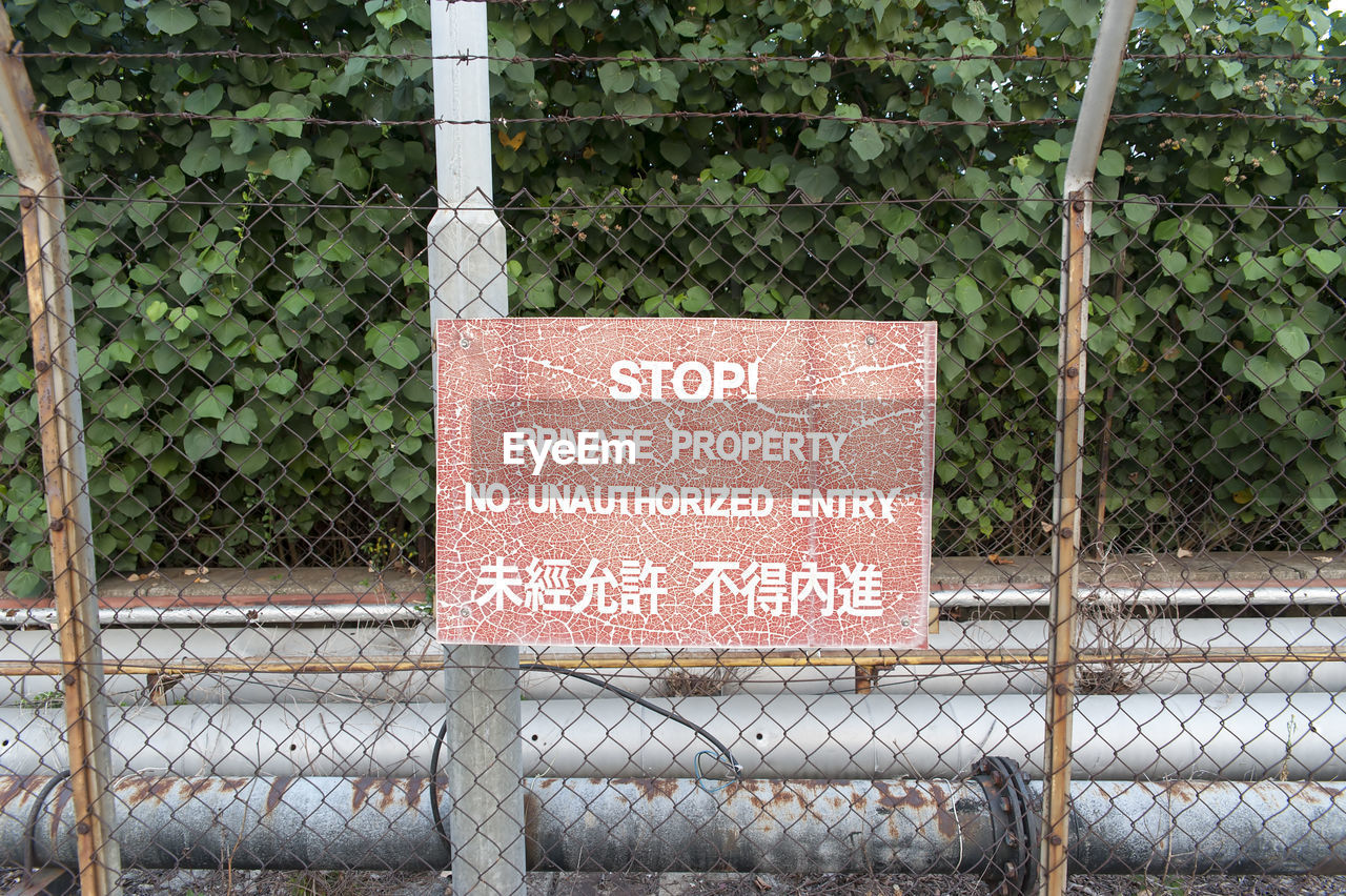 text, communication, western script, sign, fence, barrier, information, boundary, no people, security, chainlink fence, warning sign, protection, information sign, safety, metal, day, plant, nature, script, outdoors, message