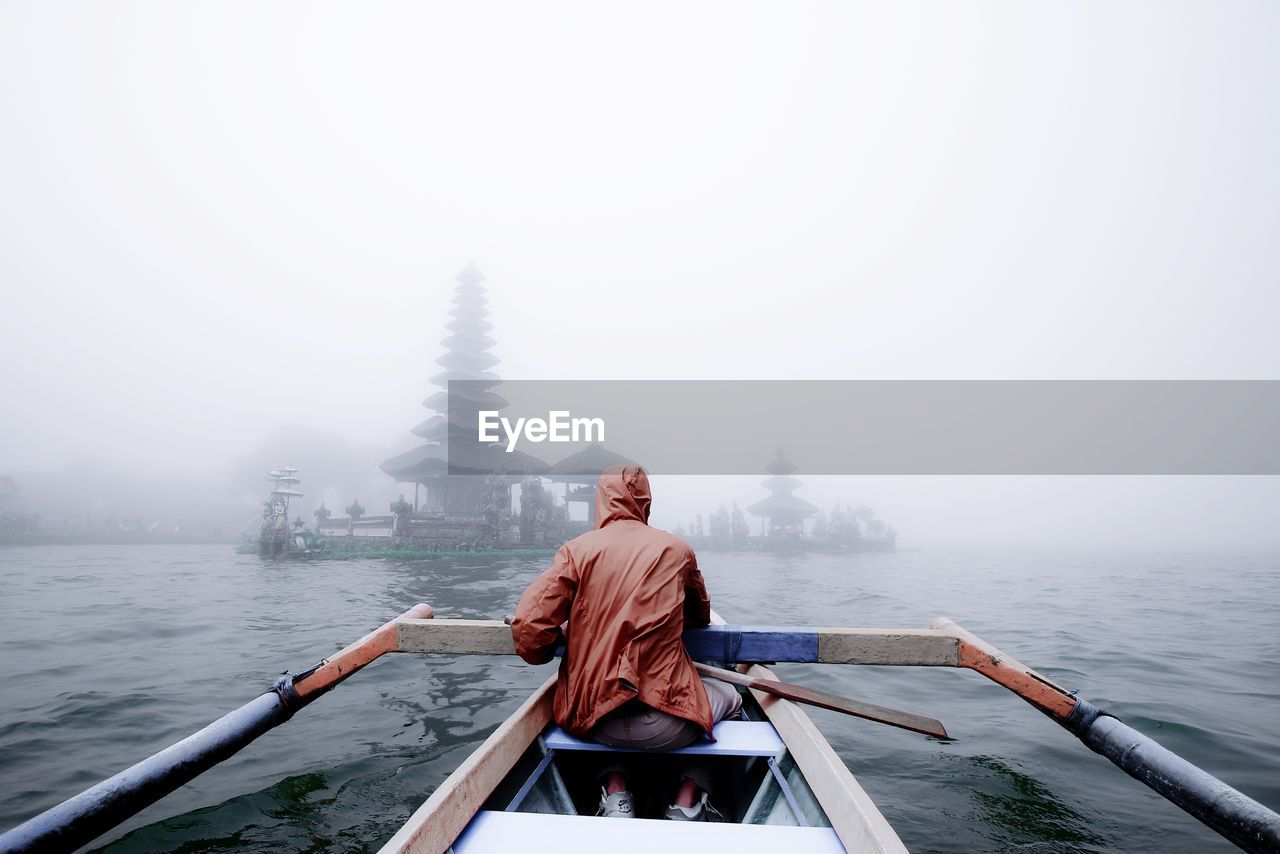 fog, nautical vessel, water, transportation, mode of transportation, real people, one person, rear view, sky, nature, beauty in nature, day, lifestyles, scenics - nature, men, leisure activity, travel, outdoors, rain
