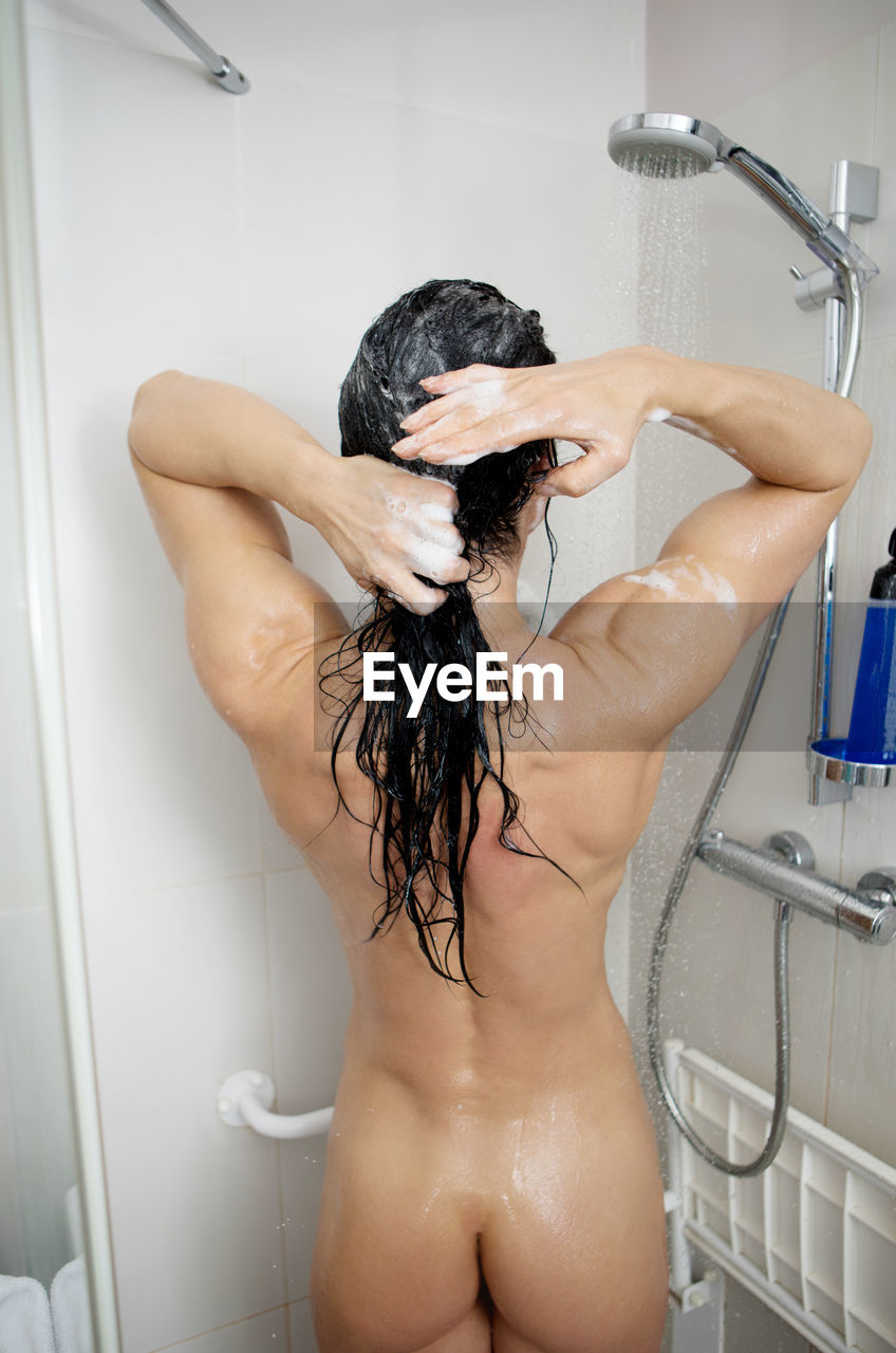 Rear view of naked muscular woman taking bath in bathroom