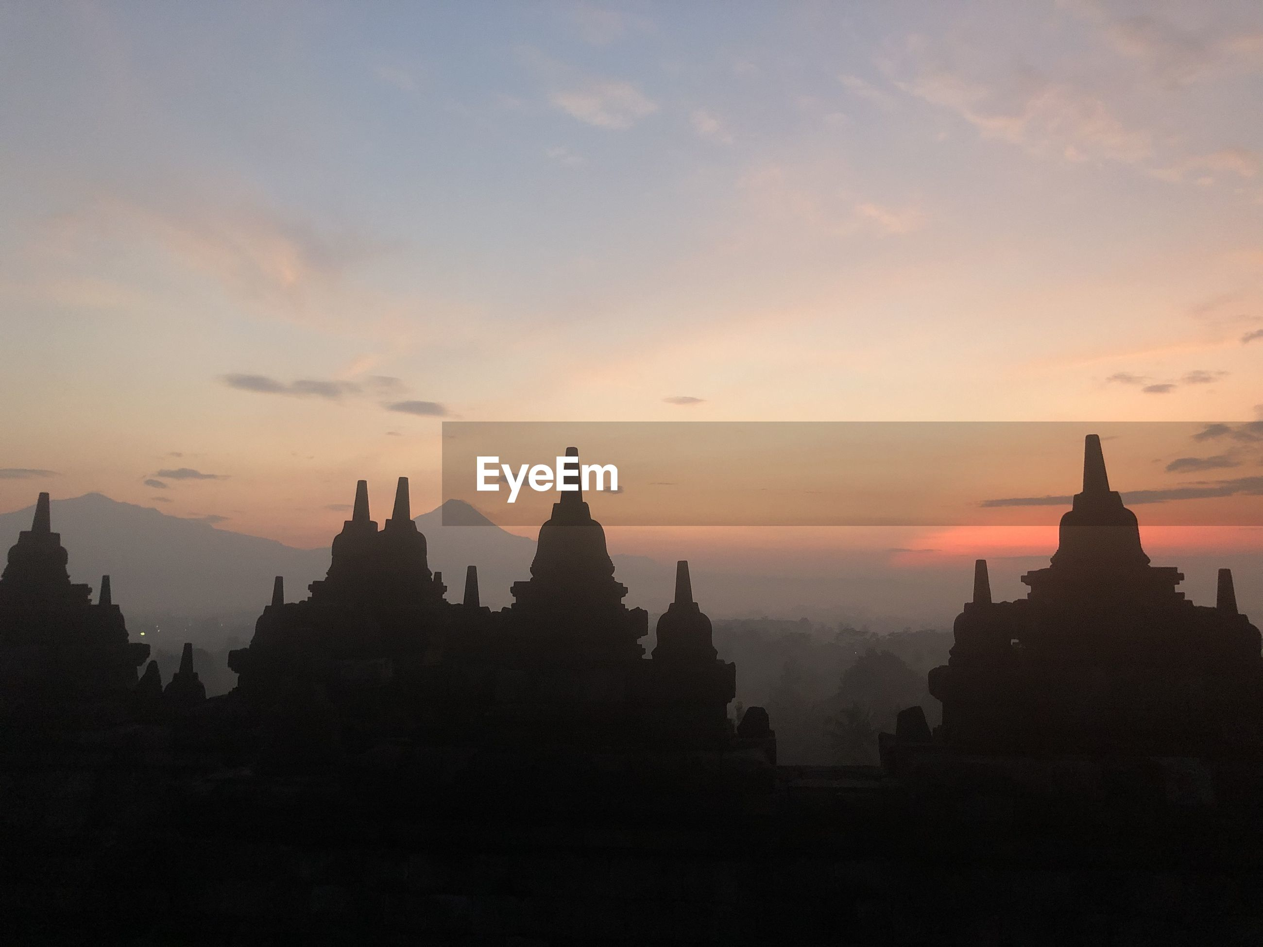 PANORAMIC VIEW OF A TEMPLE AGAINST SKY DURING SUNSET