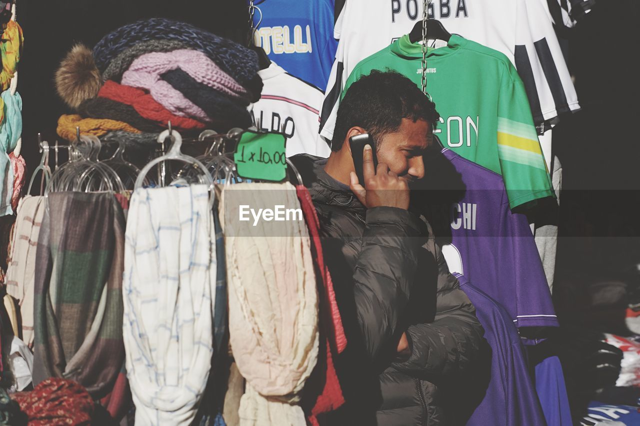 retail, real people, casual clothing, choice, one person, day, men, coathanger, warm clothing, outdoors, young adult, people