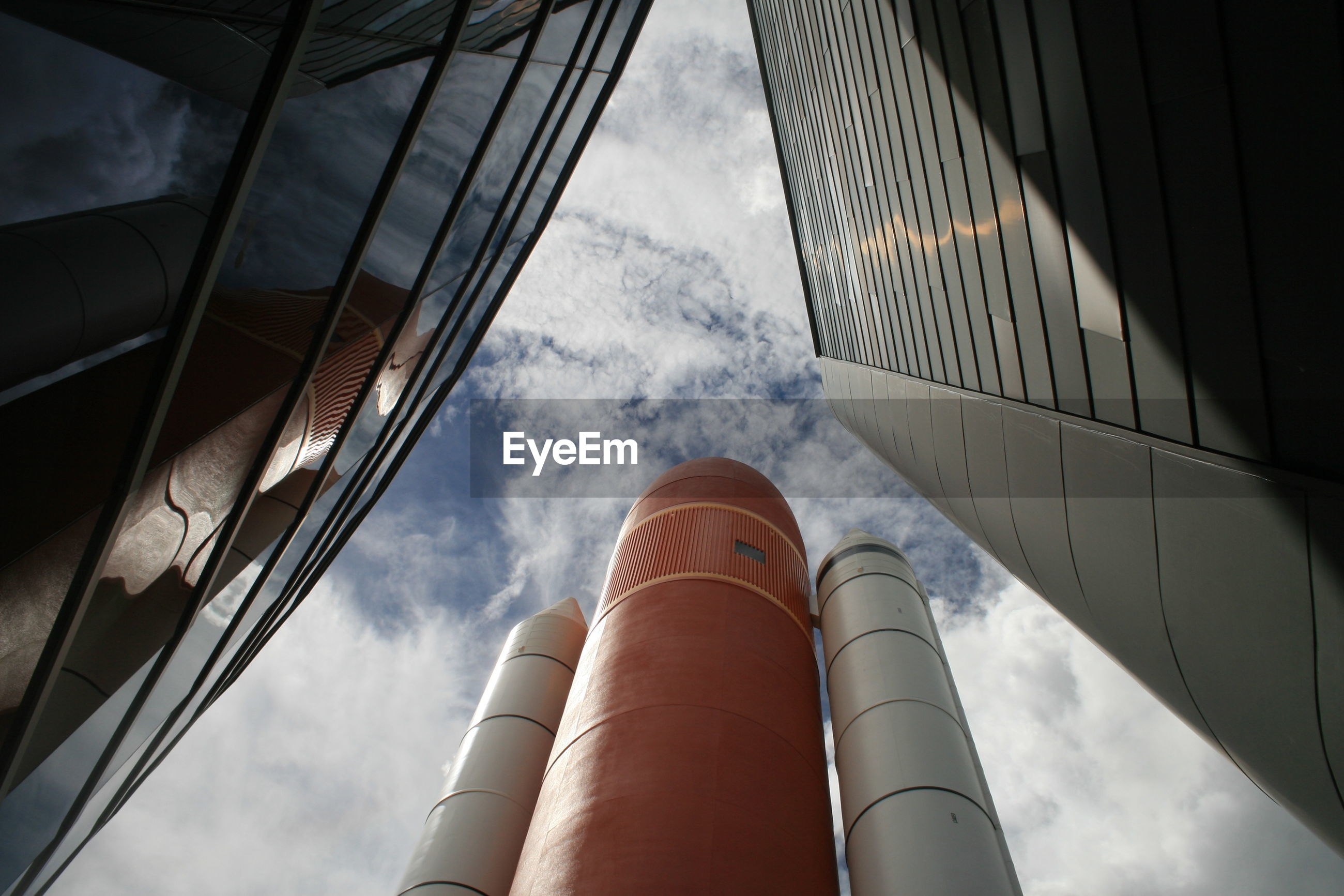 Low angle view of rocket against cloudy sky in kennedy space center