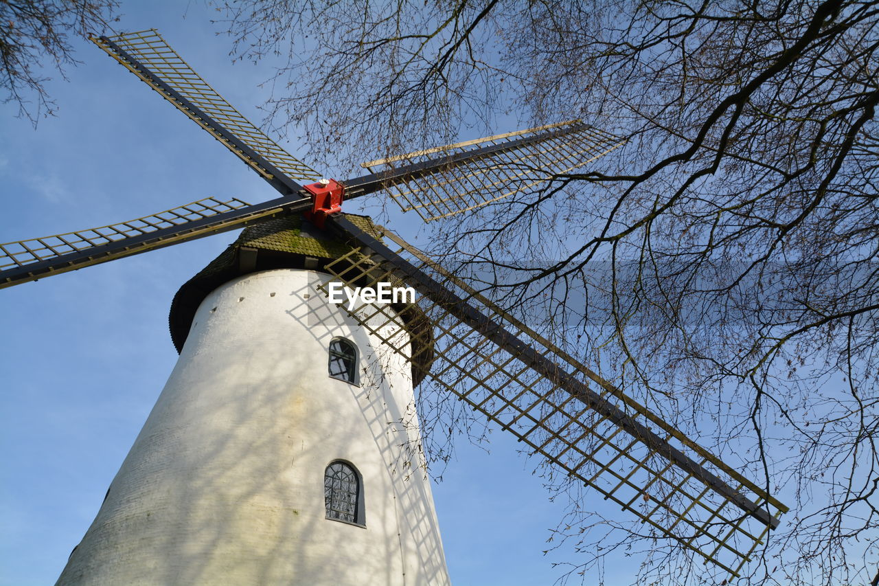 Low Angle View Of Traditional Windmill By Bare Trees Against Sky