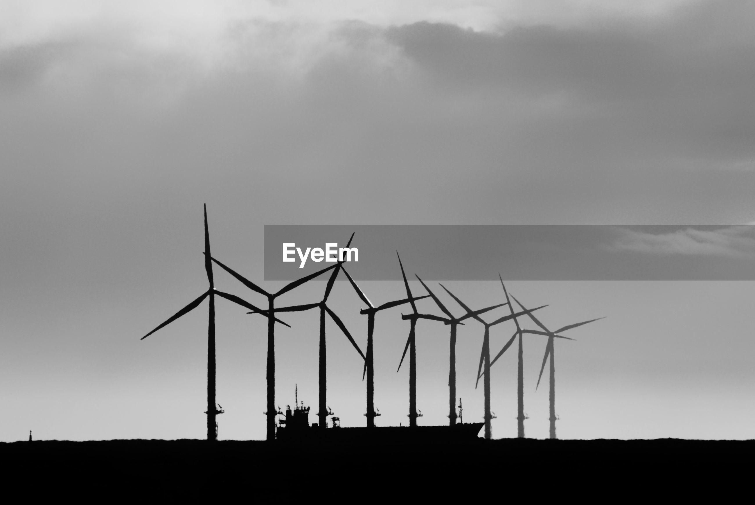 Windmills on land against sky