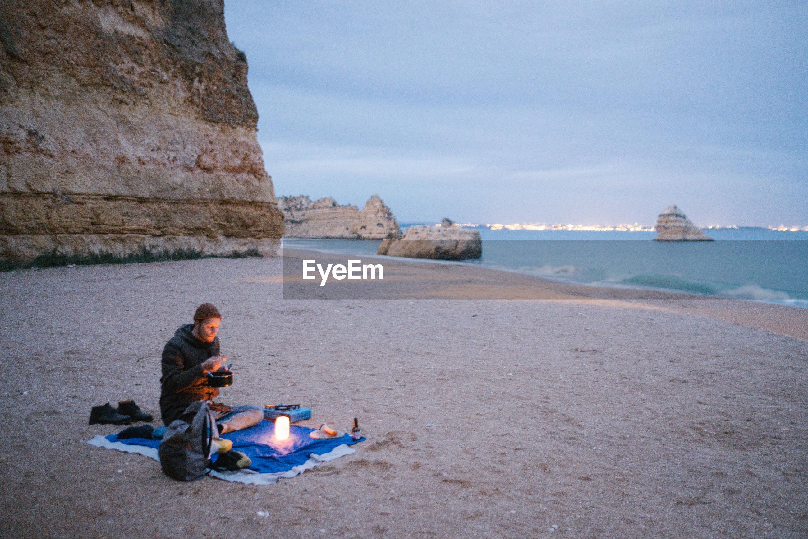 Young man sitting at beach