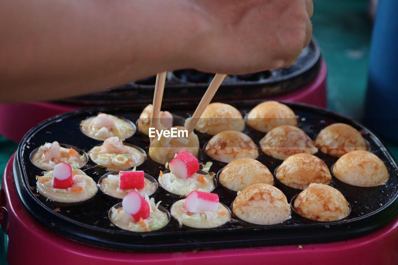 Cropped Hand Of Person Holding Takoyaki With Chopsticks