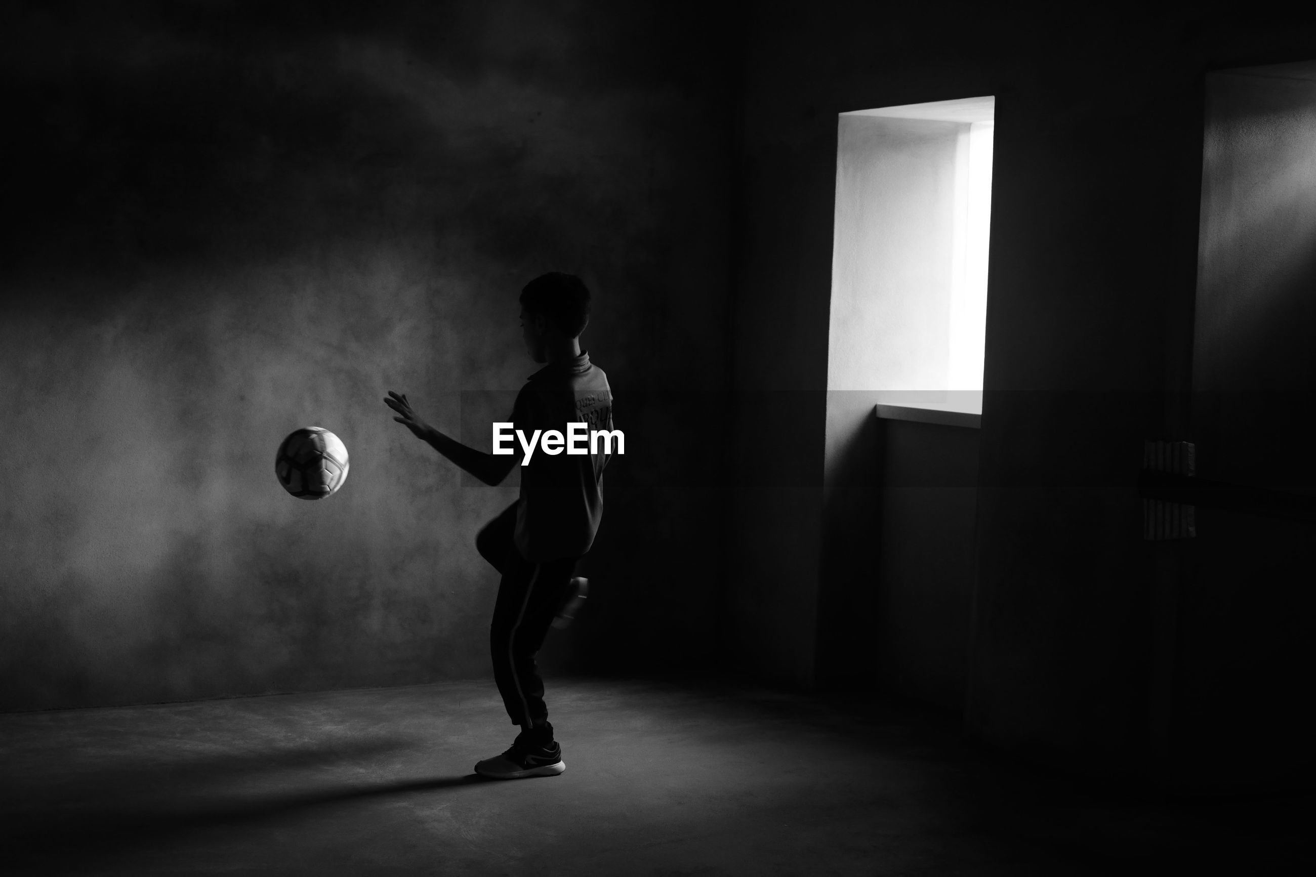 one person, real people, full length, indoors, ball, standing, lifestyles, playing, sport, skill, leisure activity, men, soccer, illuminated, performance, holding, soccer ball, wall - building feature, young adult, stage