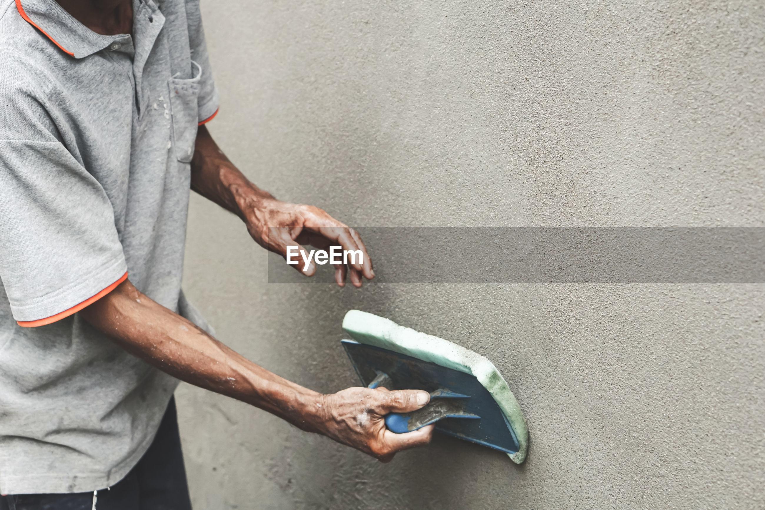 Asian male worker plasterer using a plastering sponge float on an outdoor cement wall
