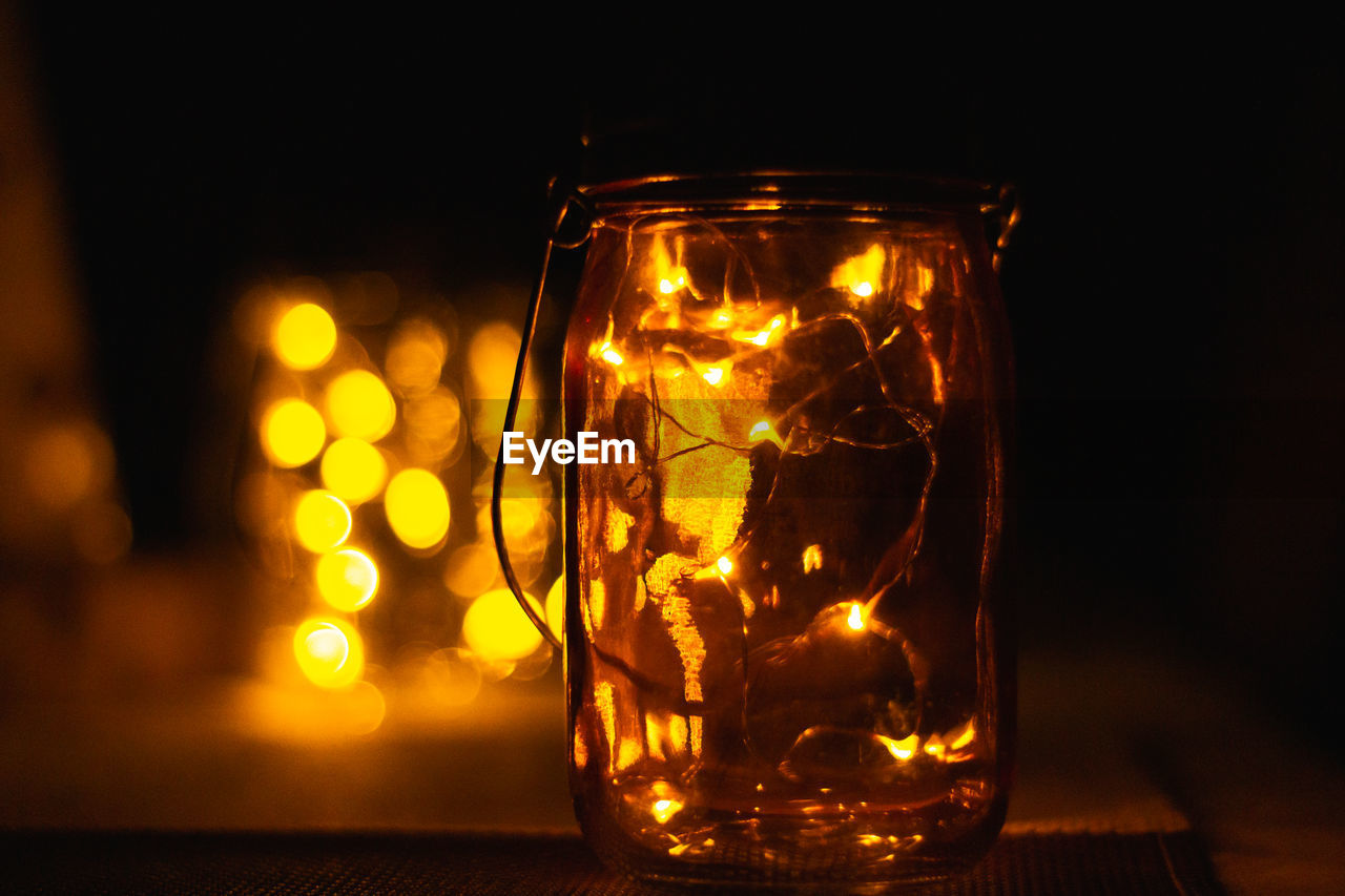 transparent, glass - material, illuminated, close-up, indoors, table, glass, lighting equipment, jar, no people, still life, focus on foreground, container, glowing, night, drinking glass, food and drink, light, orange color, electric light, dark