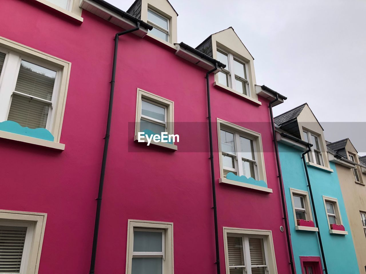 window, architecture, building exterior, built structure, building, low angle view, residential district, pink color, no people, day, outdoors, red, house, multi colored, city, in a row, side by side, pattern, nature, apartment, row house