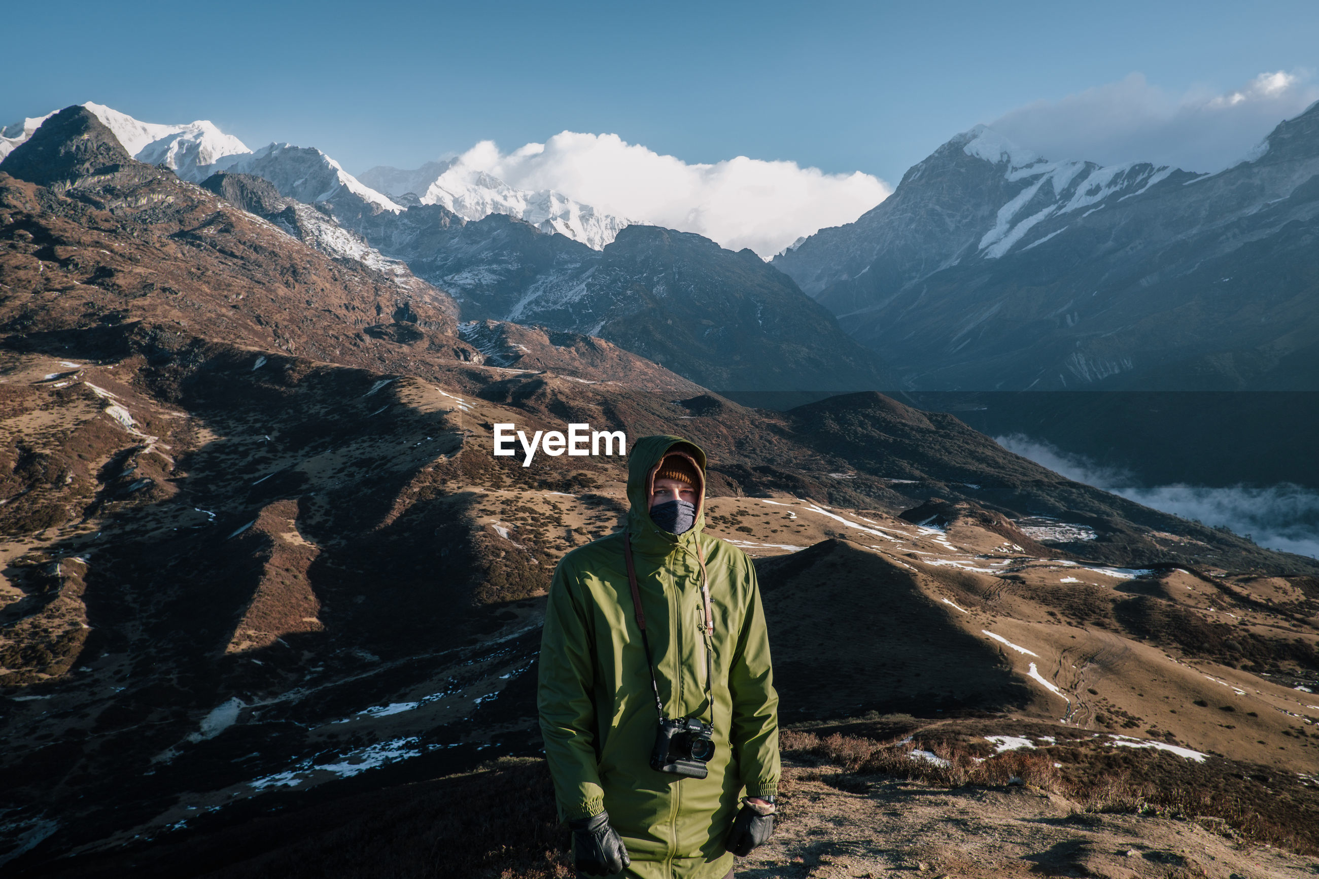 MAN STANDING BY MOUNTAINS AGAINST SKY