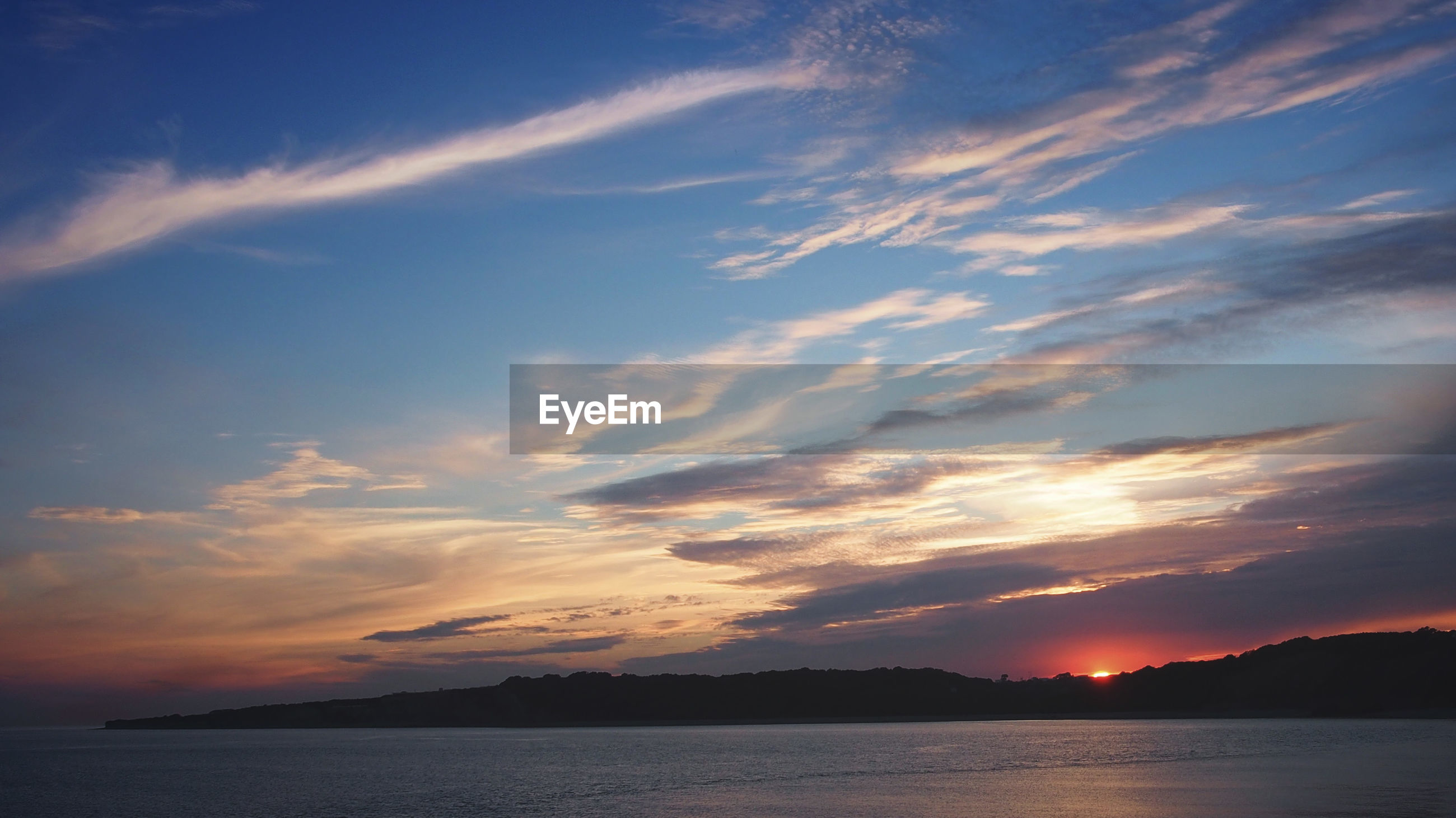 Scenic view of sea by mountains against cloudy sky during sunset