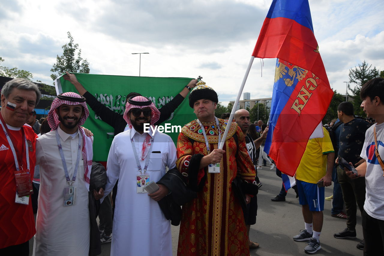 real people, group of people, crowd, men, women, large group of people, leisure activity, lifestyles, adult, flag, standing, day, patriotism, celebration, sky, cloud - sky, traditional clothing, nature, outdoors, festival