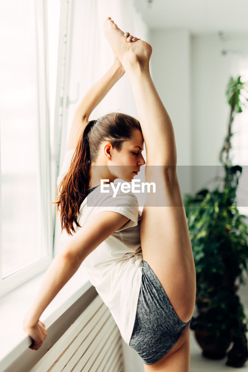 Full Length Rear View Of Young Woman Stretching Legs By Window At Home