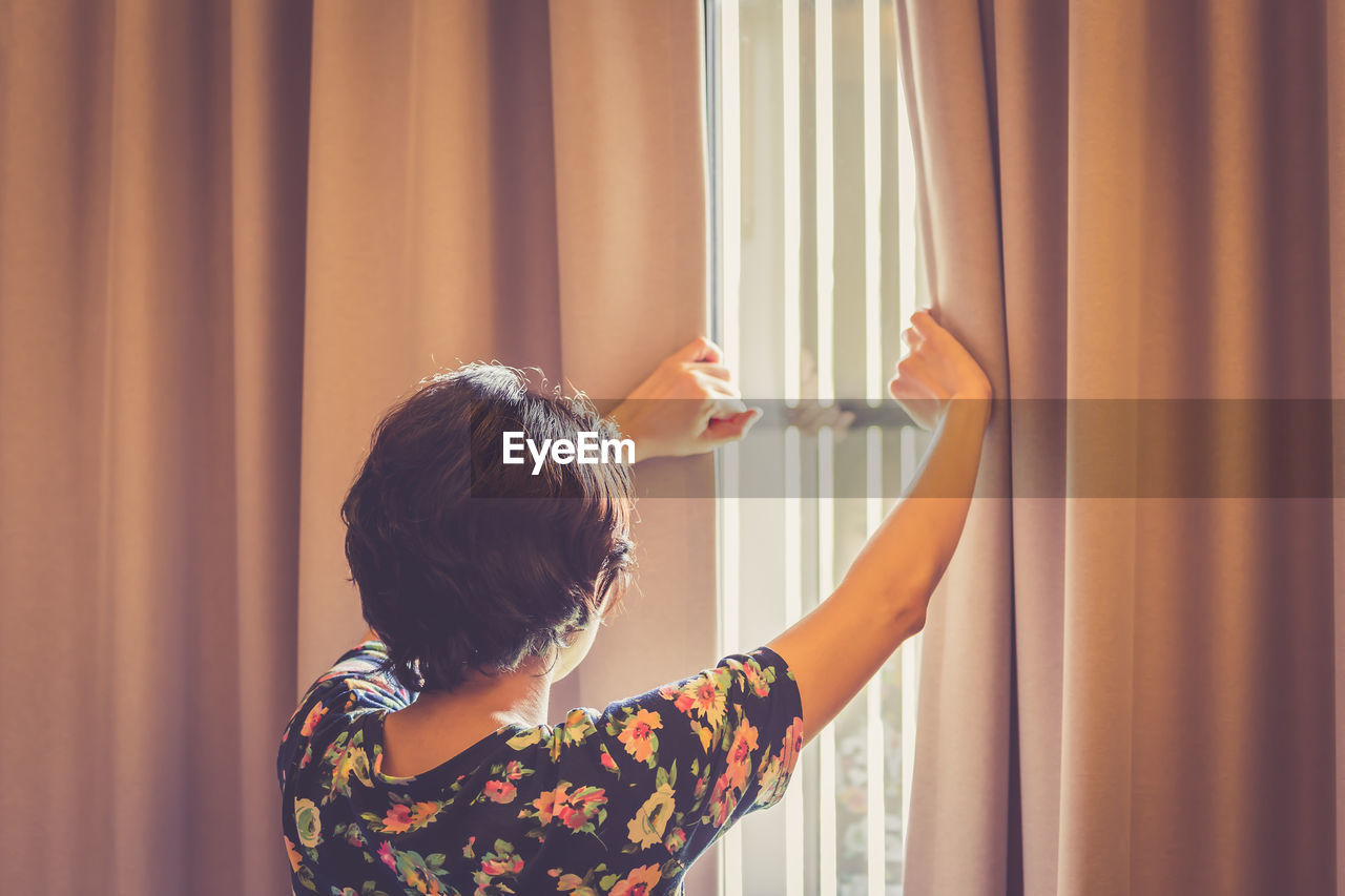 Rear View Of Mature Woman Looking Through Window At Home