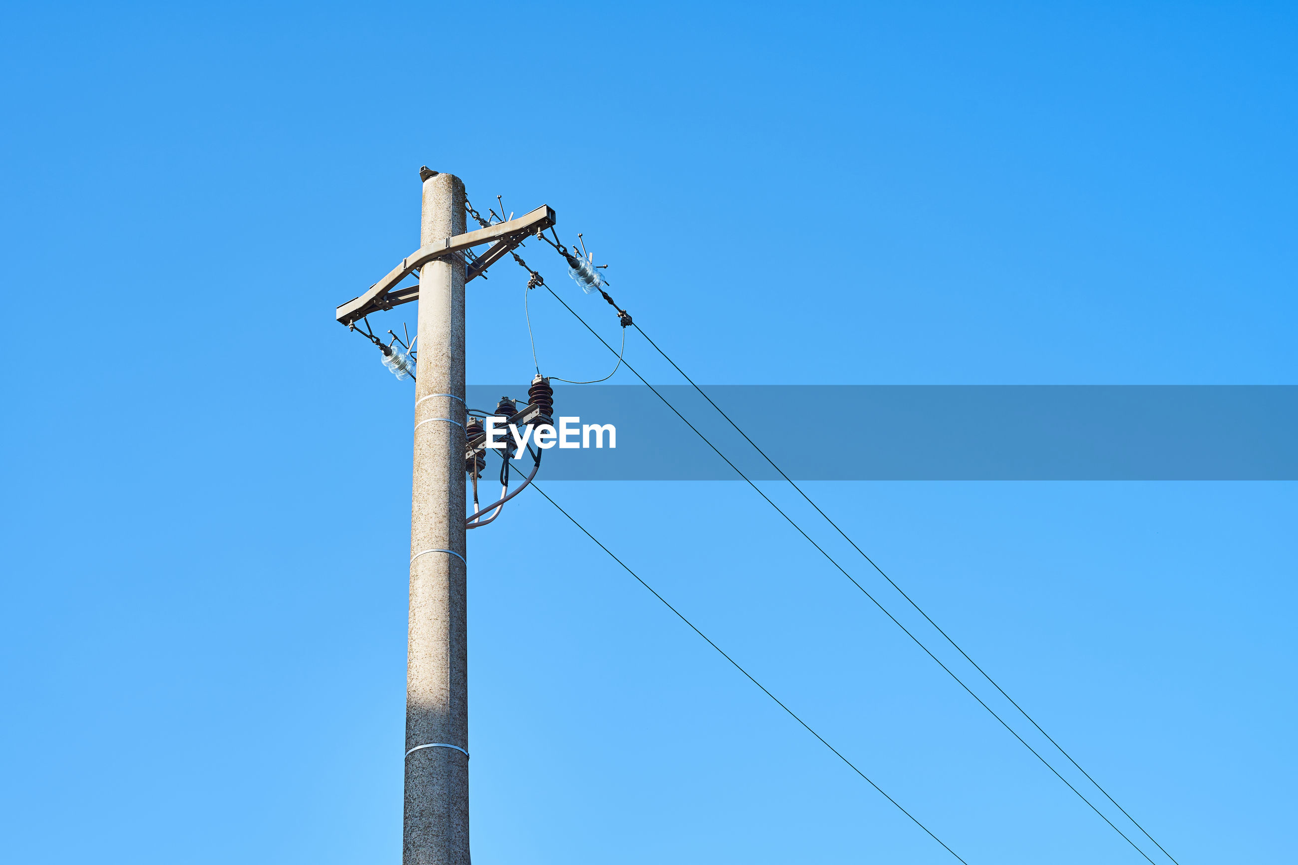 Low angle view of power lines against clear blue sky