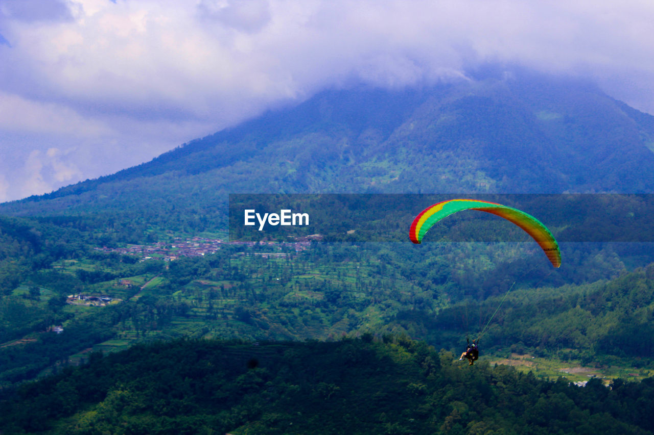 adventure, extreme sports, cloud - sky, sport, mountain, paragliding, parachute, environment, beauty in nature, sky, mid-air, nature, scenics - nature, plant, leisure activity, landscape, day, unrecognizable person, flying, tranquil scene, freedom, mountain range, outdoors