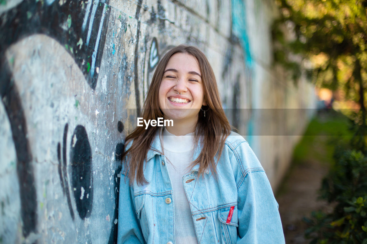 PORTRAIT OF A SMILING YOUNG WOMAN STANDING AGAINST GRAFFITI
