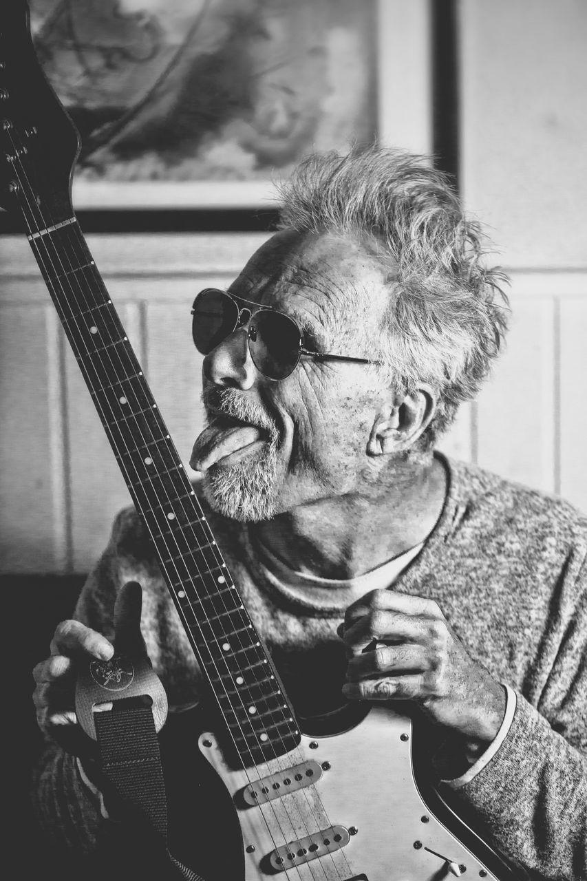 Mature man licking guitar