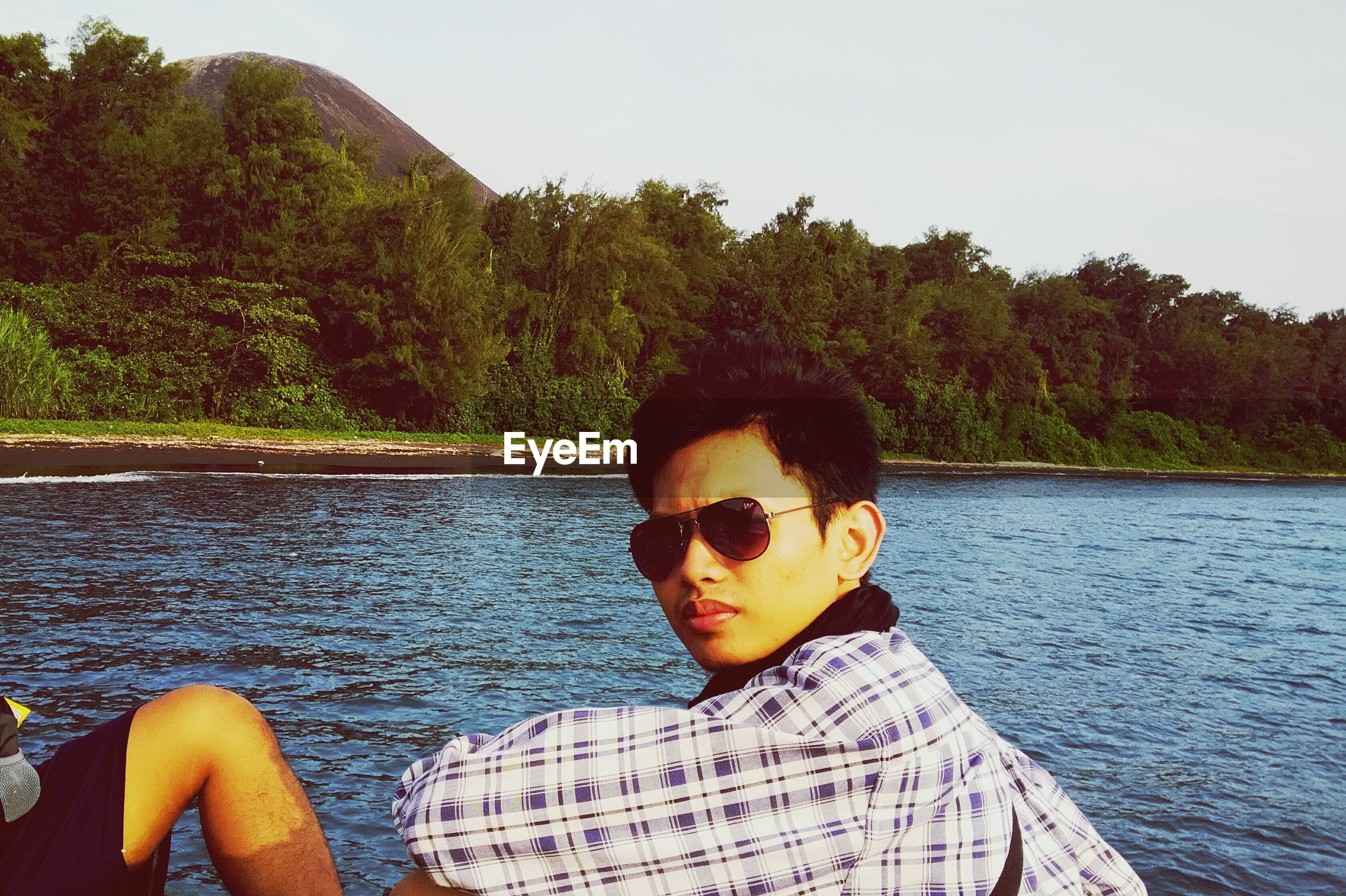 Portrait of young man wearing sunglasses against lake