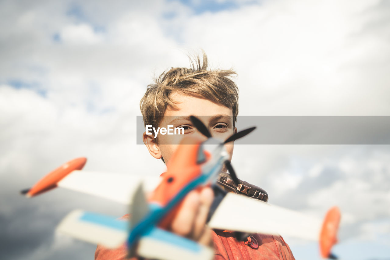 Portrait of boy playing with toy airplane against sky