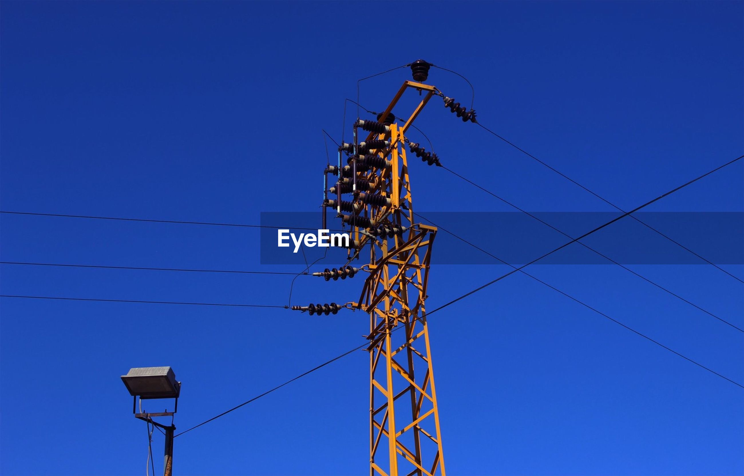 LOW ANGLE VIEW OF ELECTRICITY PYLONS AGAINST CLEAR BLUE SKY