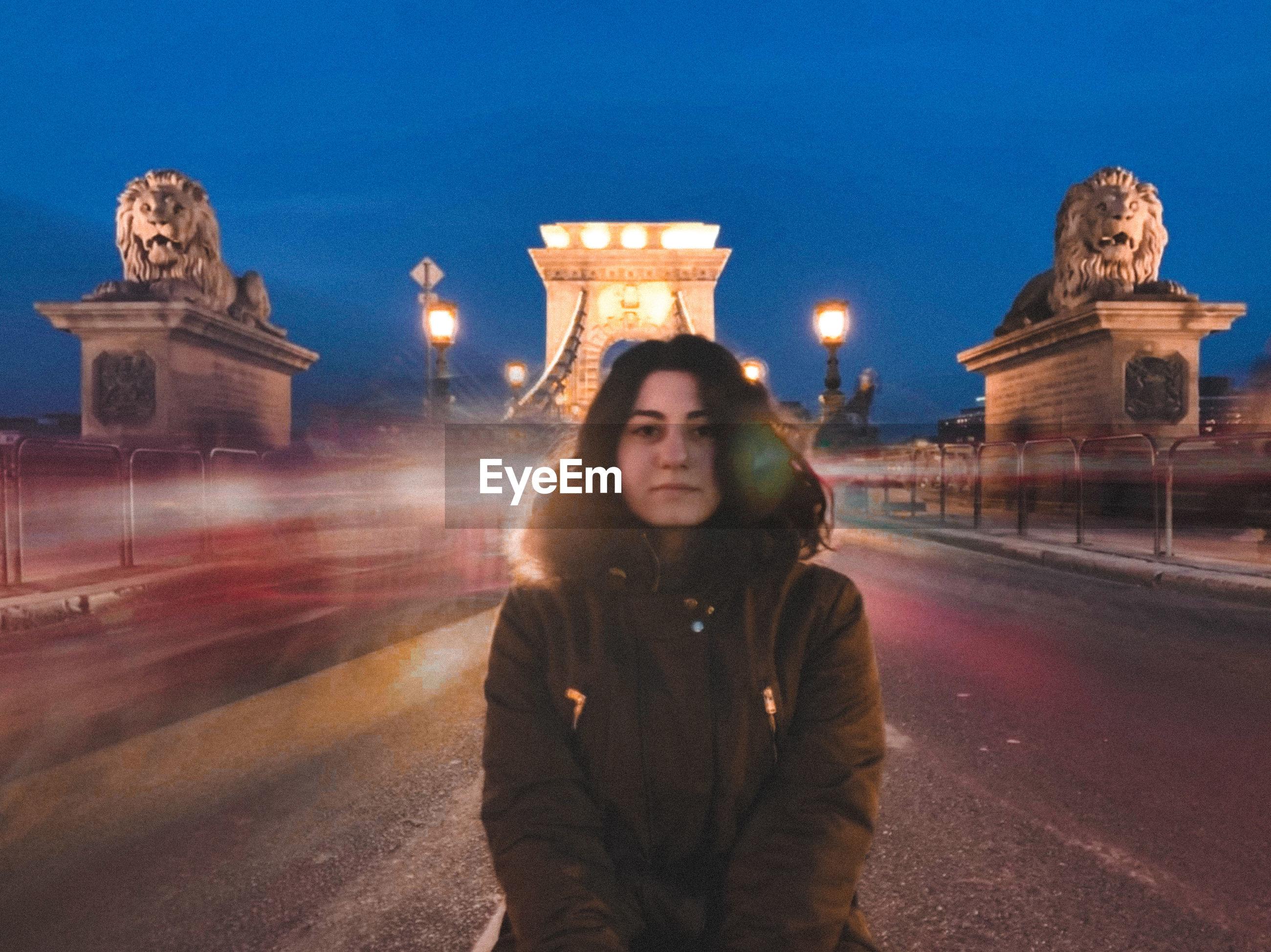 Woman standing on illuminated city at night