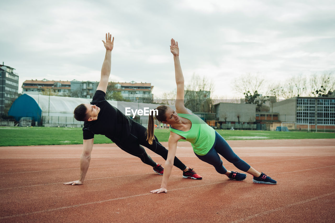 Full length of man and woman exercising on sports track