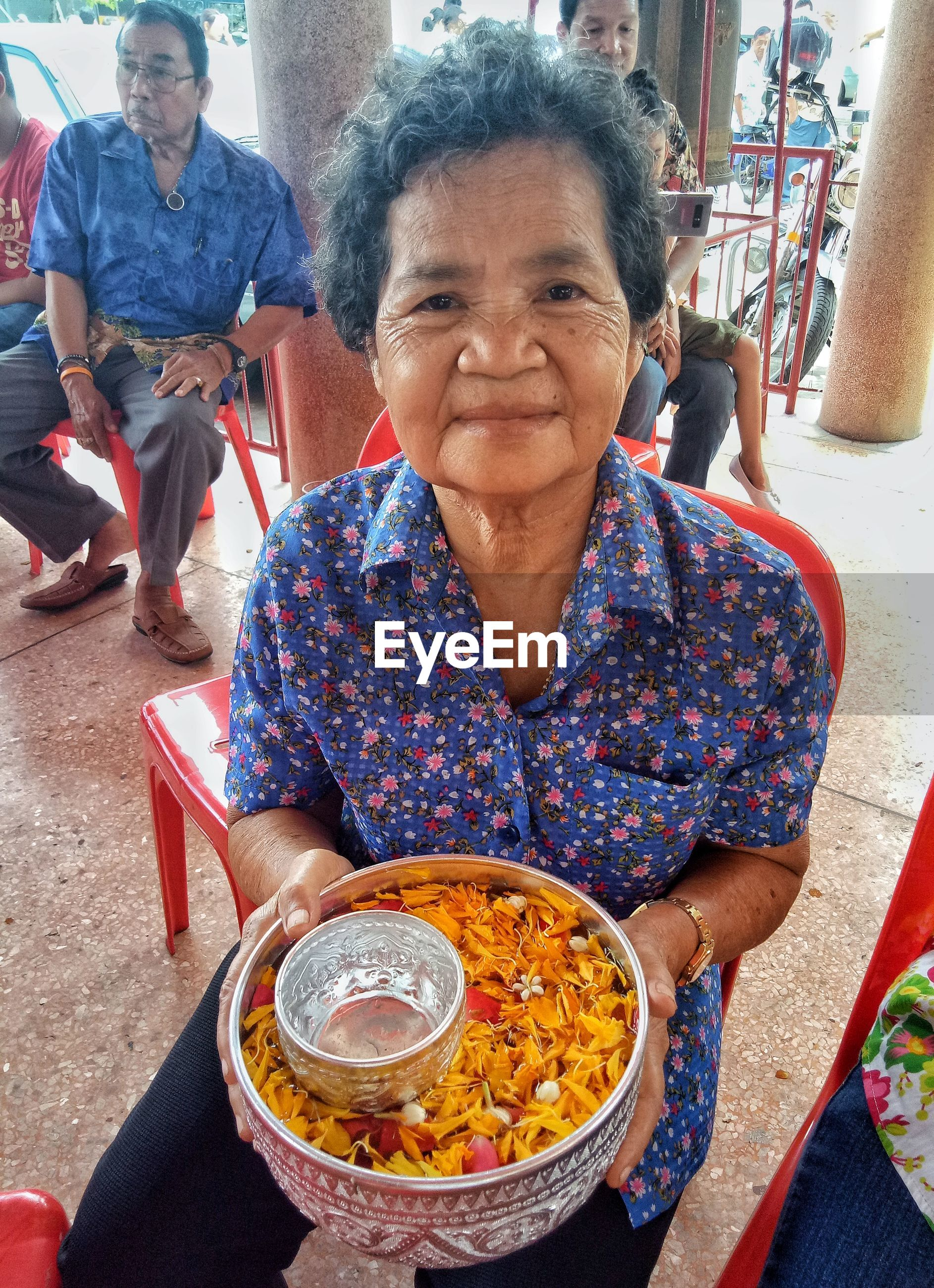 Portrait of smiling mature woman holding religious offerings in container