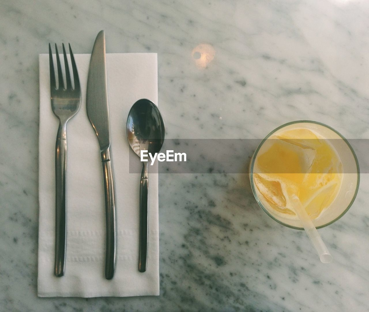 Directly above shot fresh orange juice with cutlery on marble