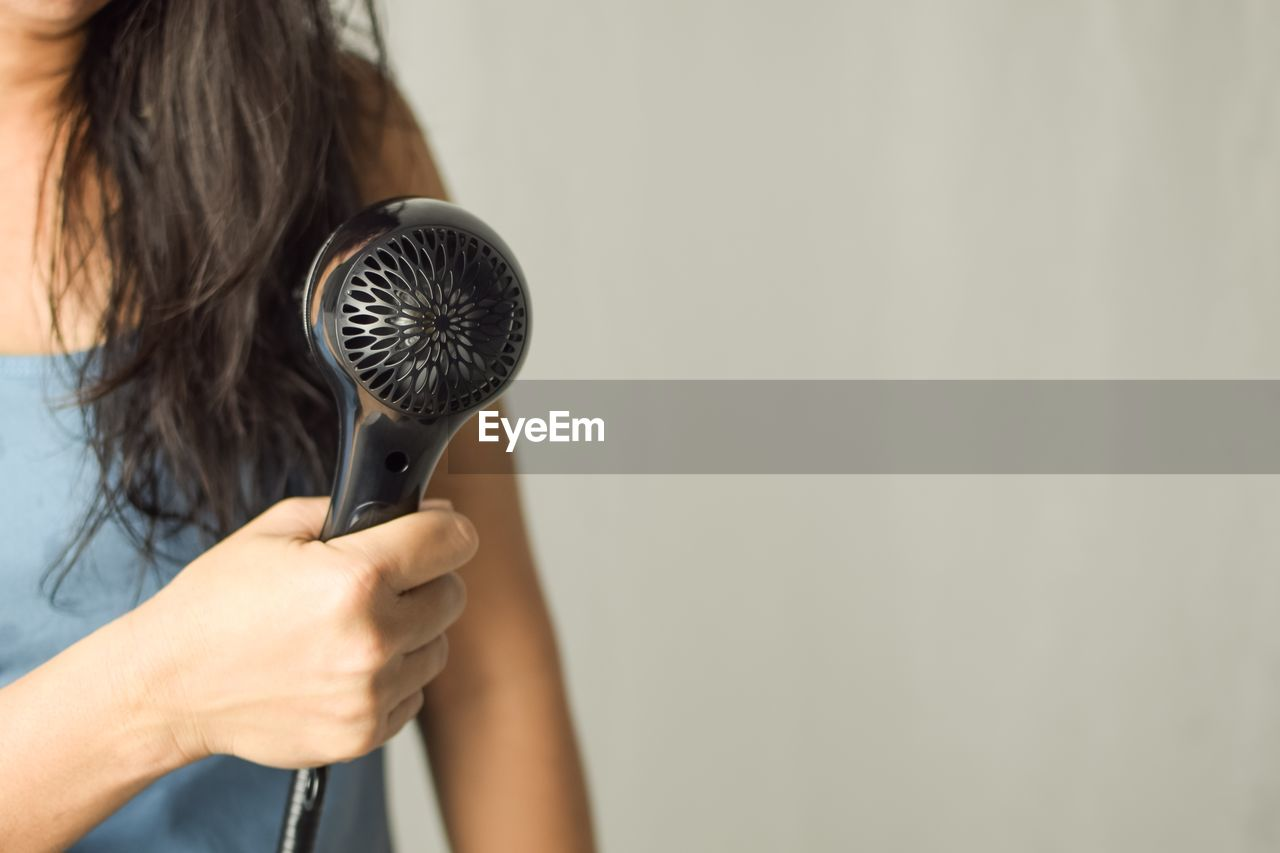 Midsection of woman holding hair dryer against white background