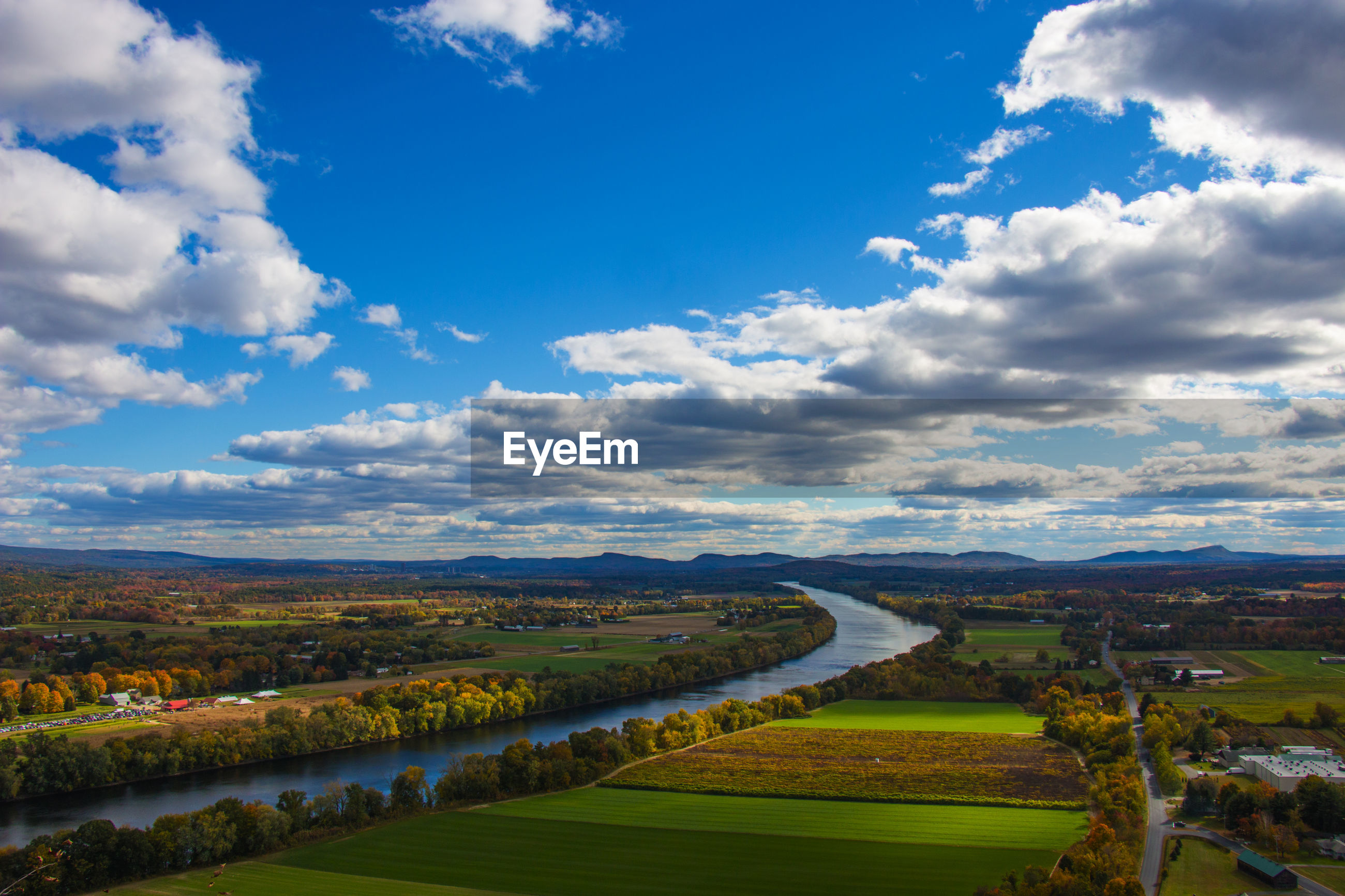 Scenic view of river amidst field against cloudy sky