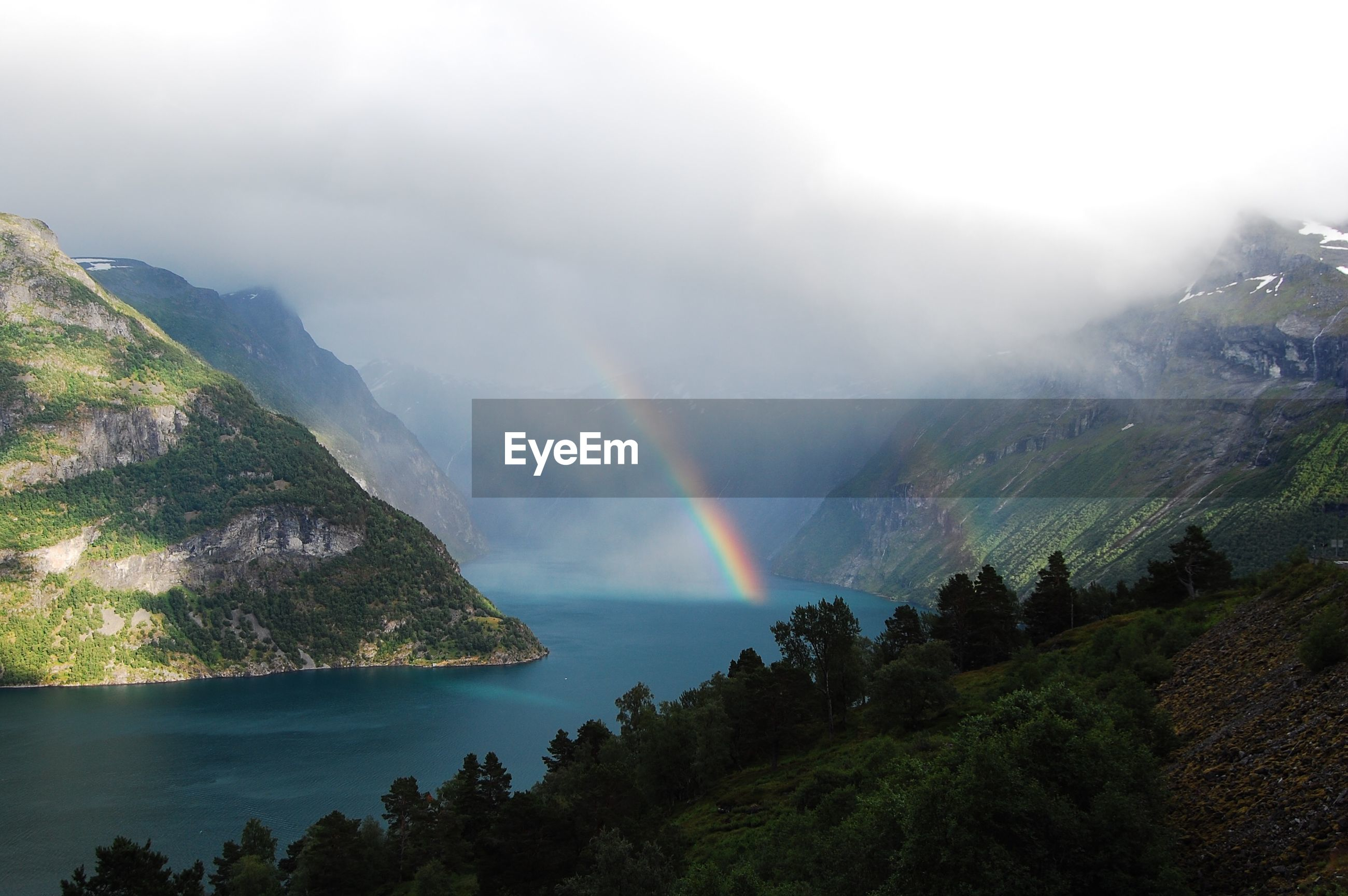 SCENIC VIEW OF RAINBOW AND MOUNTAINS AGAINST SKY
