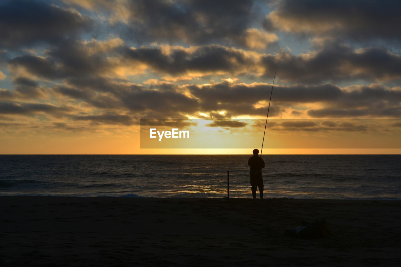 sunset, sea, silhouette, nature, horizon over water, beauty in nature, water, standing, beach, scenics, real people, one person, tranquil scene, sky, weekend activities, tranquility, fishing, cloud - sky, leisure activity, fishing pole, men, sand, full length, outdoors, one man only, people