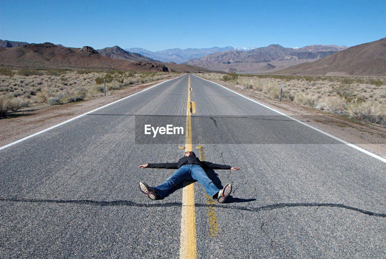 Man lying on road in desert