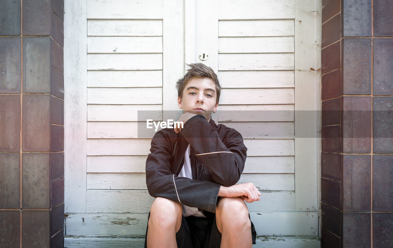 Portrait Of Confident Teenage Boy Sitting Against Closed Doors