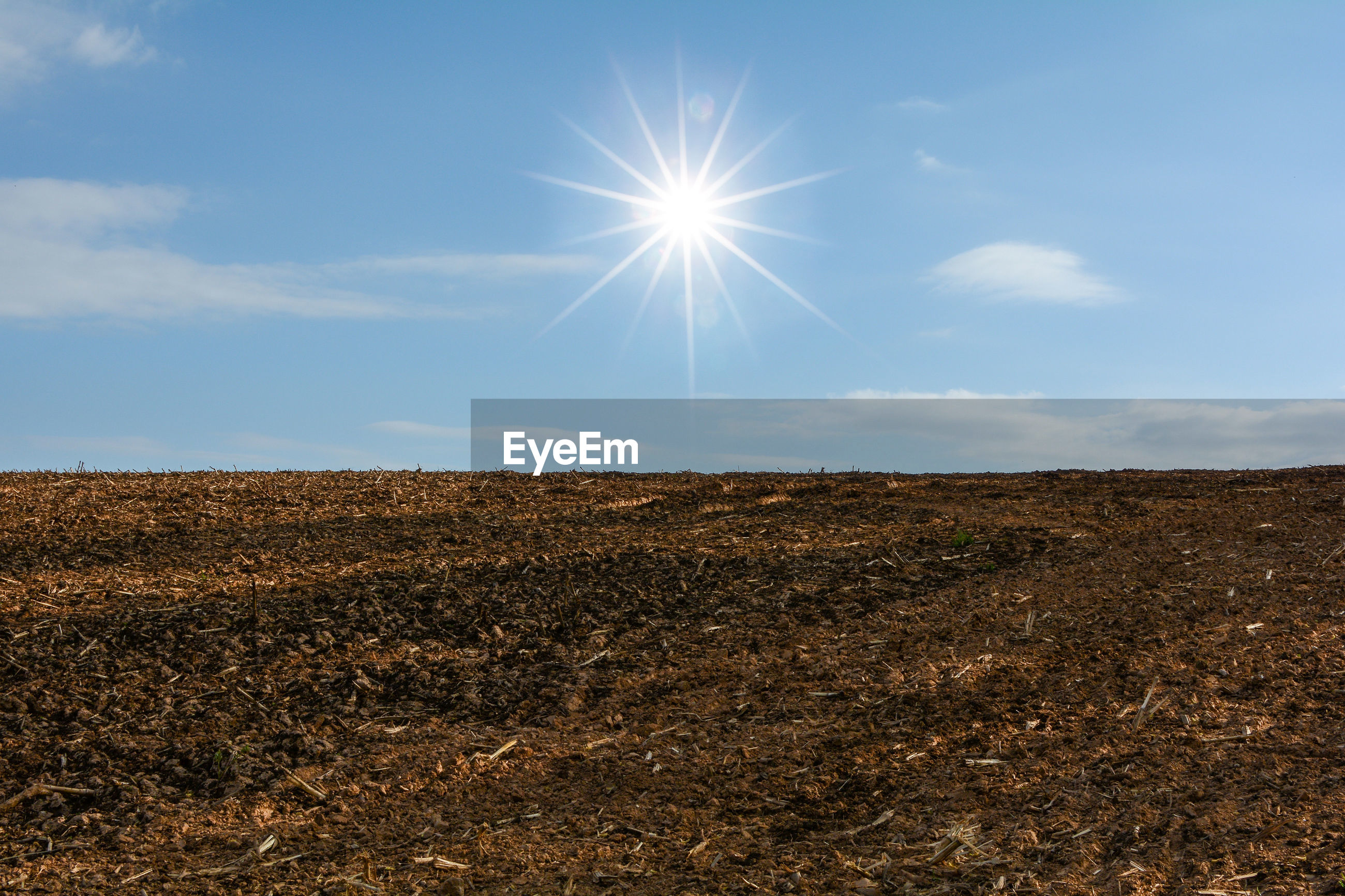 Soil from a cultivated field on a dry day with blue sky and copy space