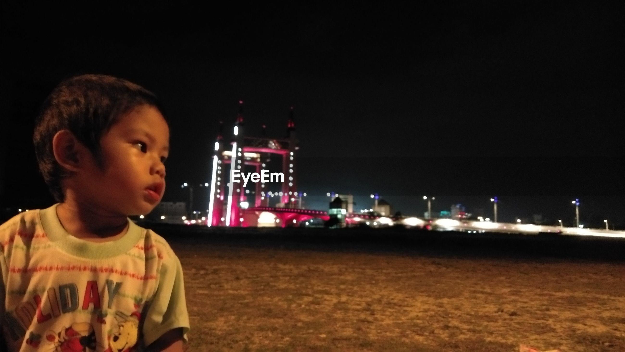PORTRAIT OF BOY LOOKING AT ILLUMINATED PARK AGAINST SKY AT NIGHT AT DUSK