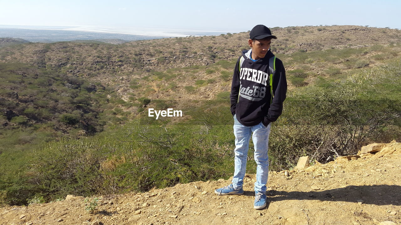 one person, casual clothing, full length, leisure activity, real people, nature, plant, lifestyles, standing, land, environment, day, beauty in nature, scenics - nature, men, mountain, young men, hiking, landscape, outdoors