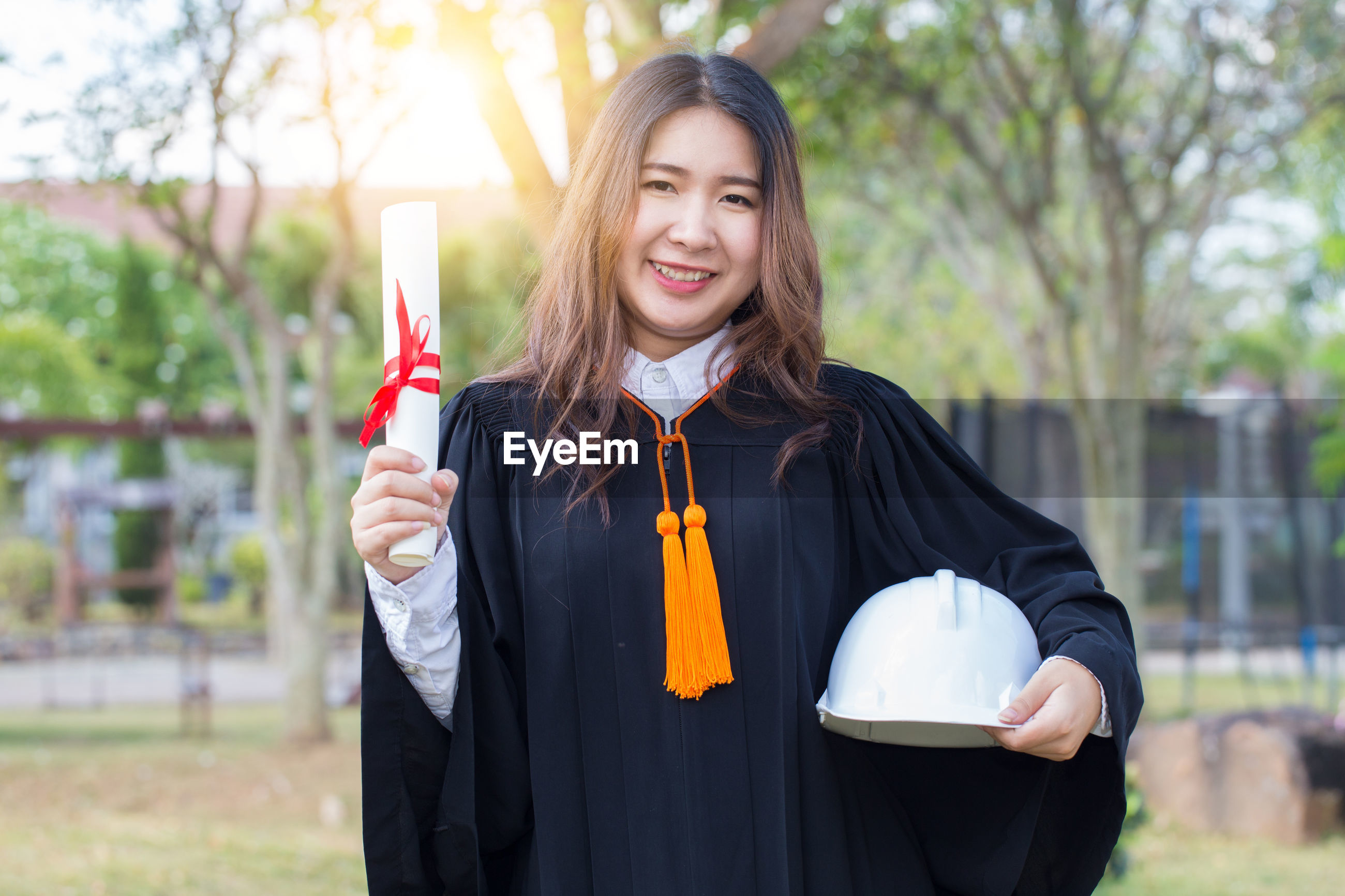 Portrait of smiling young woman wearing graduation gown while holding diploma and hardhat in park