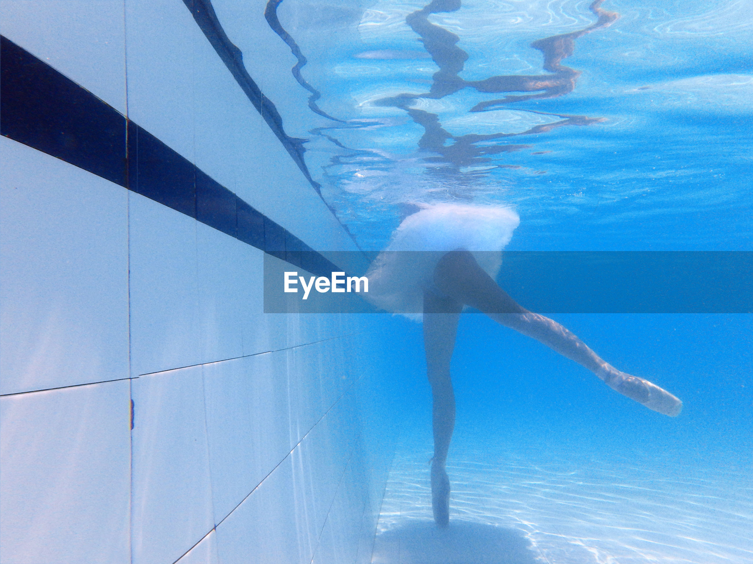 Low section of ballerina practicing in swimming pool