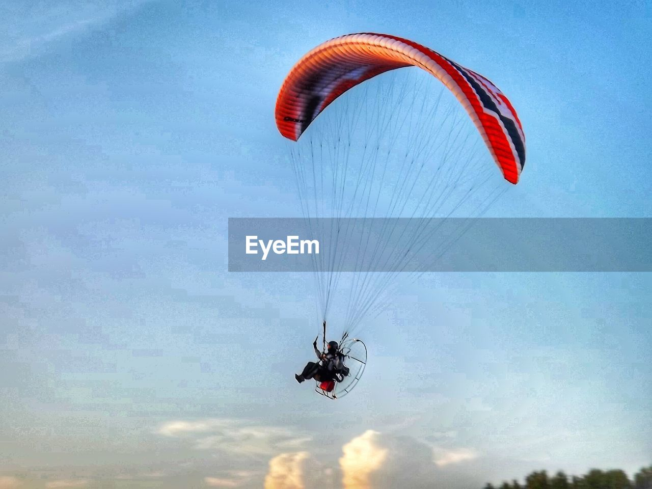 Low angle view of man flying powered parachute against sky