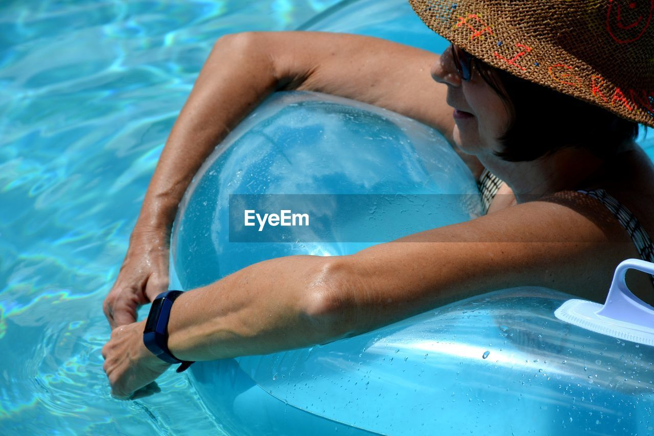High angle view of woman on inflatable in swimming pool