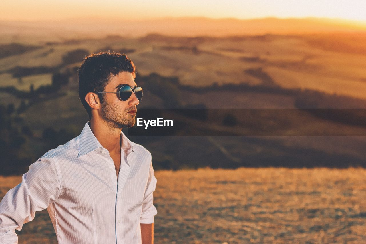 Portrait Of Man Wearing Sunglasses On Field During Sunset