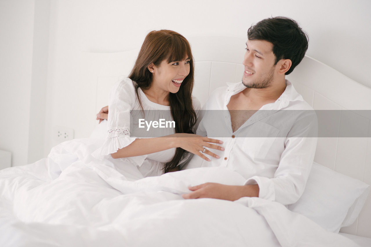 two people, young adult, togetherness, young women, love, couple - relationship, young men, bed, indoors, bonding, smiling, front view, positive emotion, women, heterosexual couple, adult, lifestyles, furniture, emotion, men