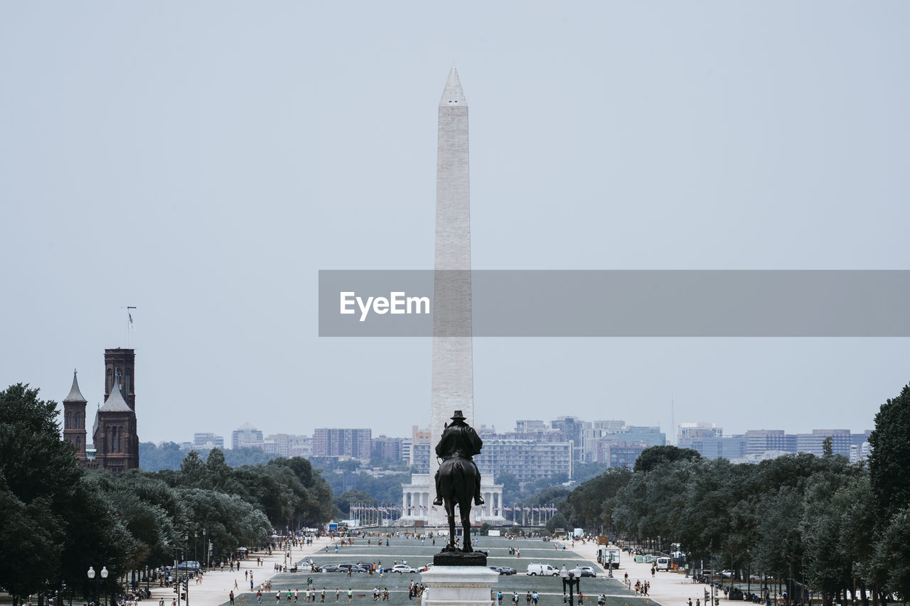 Statue Against Washington Monument In City Against Sky