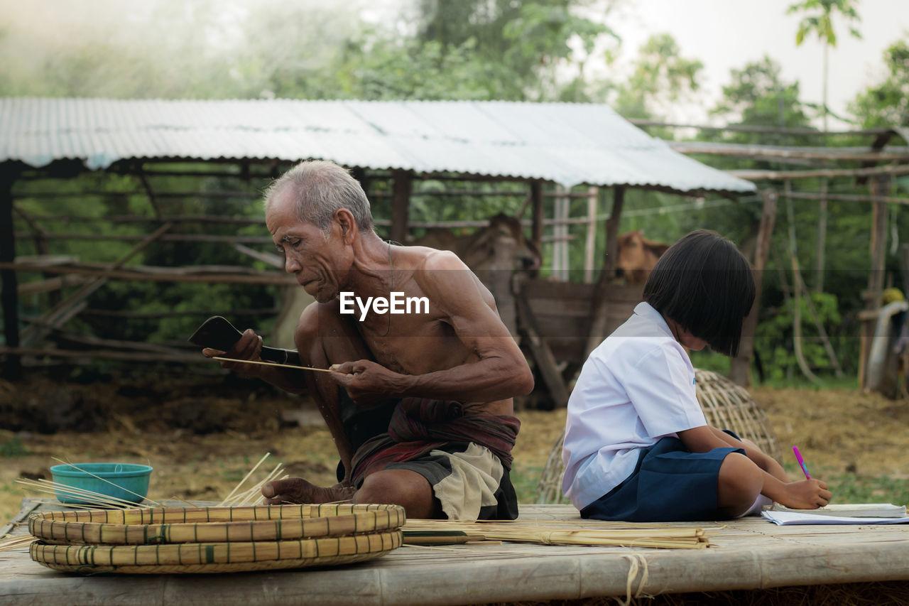 Senior Man Making Wicker Basket While Granddaughter Studying On Table