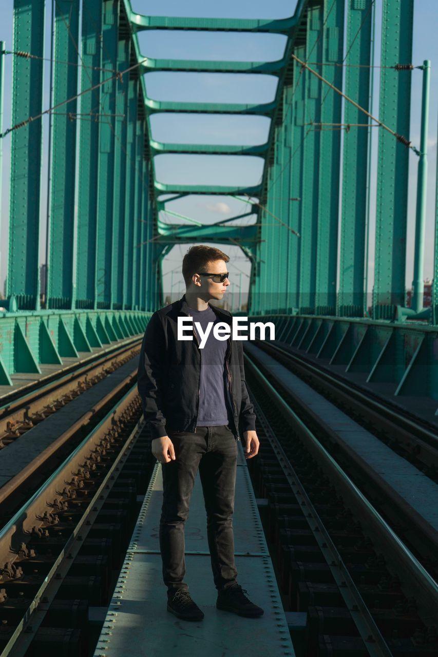 Man standing on railway bridge