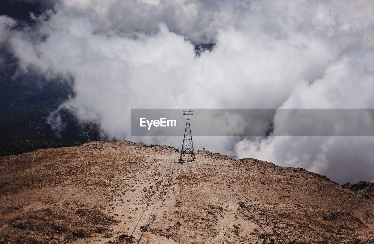 Electricity Pylon On Landscape Against Cloudy Sky